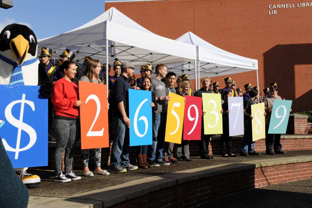 Clark students and Oswald reveal the total amount raised for Clark's Ensuring A Bright Future fundraising campaign during a campus celebration September 30.