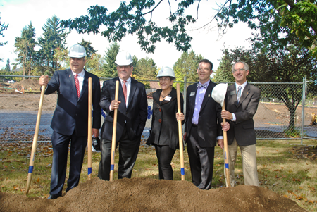 Left to right, Robert Knight, Greg Wallace, Lisa Gibert, Tim Cook and Peter Williams pose in front of the STEM building construction site.