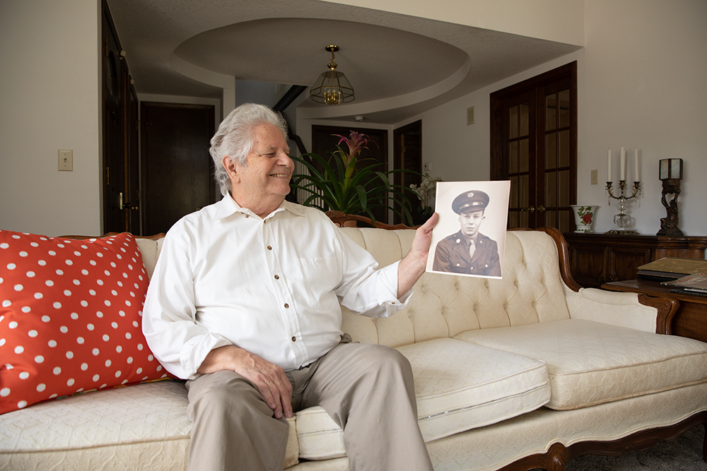 bob blanchard holds a picture of his father